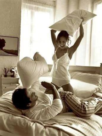 couple pillow fighting on bed playing